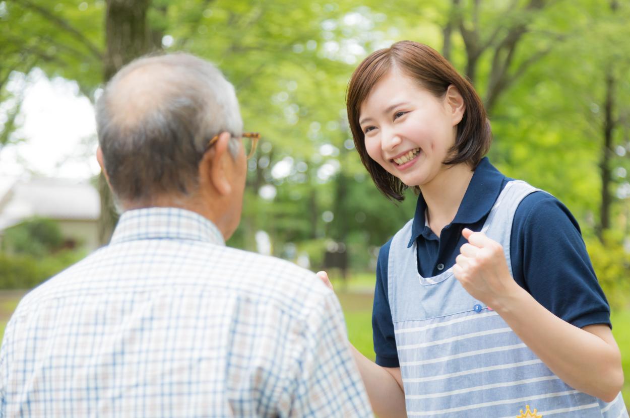 おじいさんに元気に笑いかける若い女性の介護士の写真